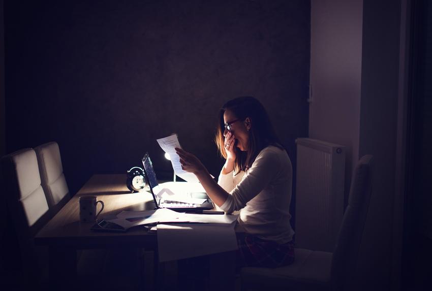 Woman working late yawning
