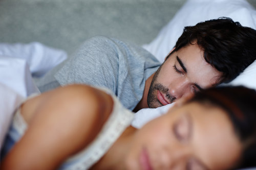 A couple are peacefully asleep side-by-side in a bed, each with their own space, thanks to the extra-wide mattress.
